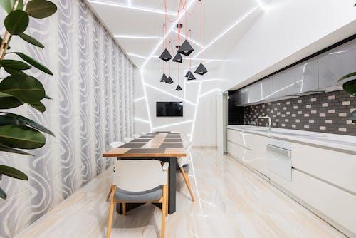 Minimalist interior of illuminated kitchen with dining zone