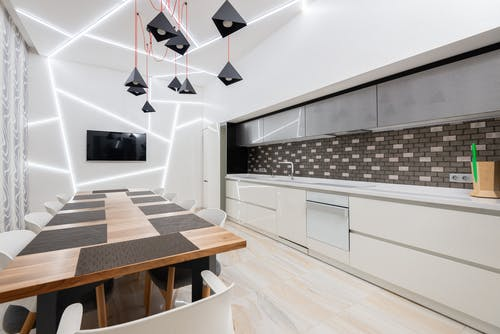 Modern kitchen interior with minimalist white cabinets and wooden table decorated with creative chandelier