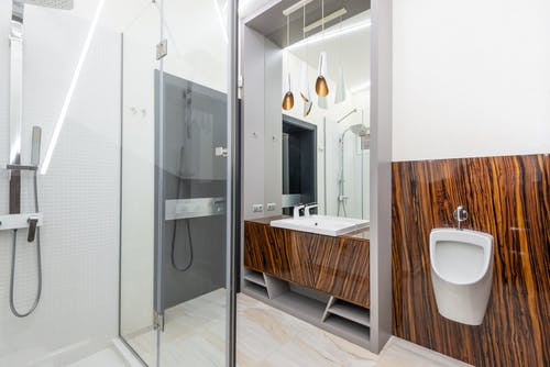 Shower cabin in modern bathroom with sink and urinal