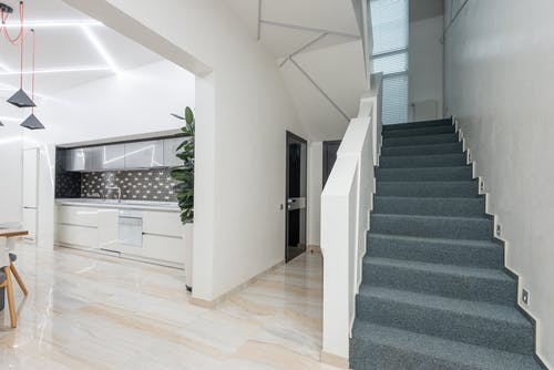 Stairway in corridor of spacious house near light kitchen with minimalist furniture and modern appliances