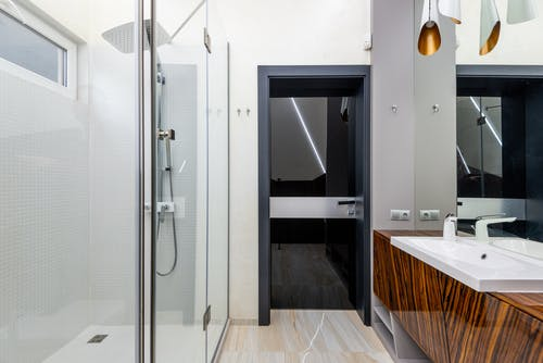 Interior of light contemporary bathroom with shower and glass door in modern apartment