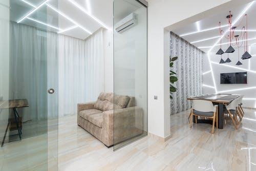 Light modern studio apartment with sofa behind glass walls and dining table under modern geometric illumination on ceiling