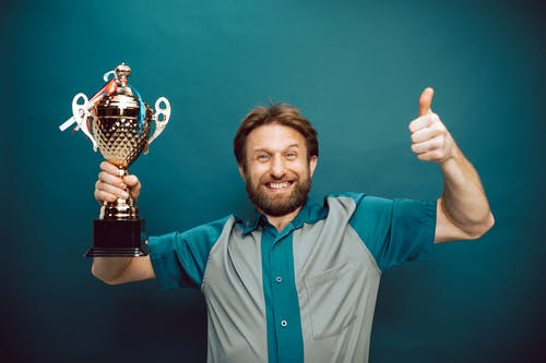 A Man's Face of Victory Holding His Trophy