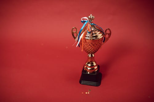 Gold and Red Trophy on Red Table