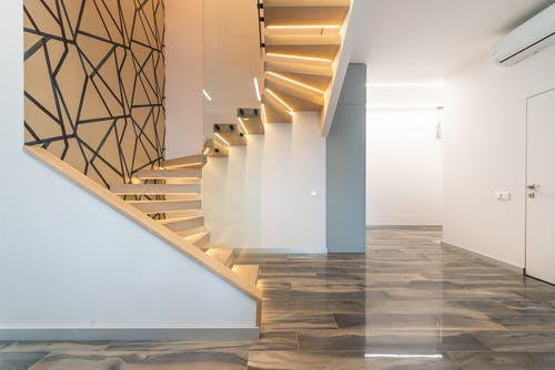 Contemporary hall interior with door against curved staircase and wall with geometric ornament in light house