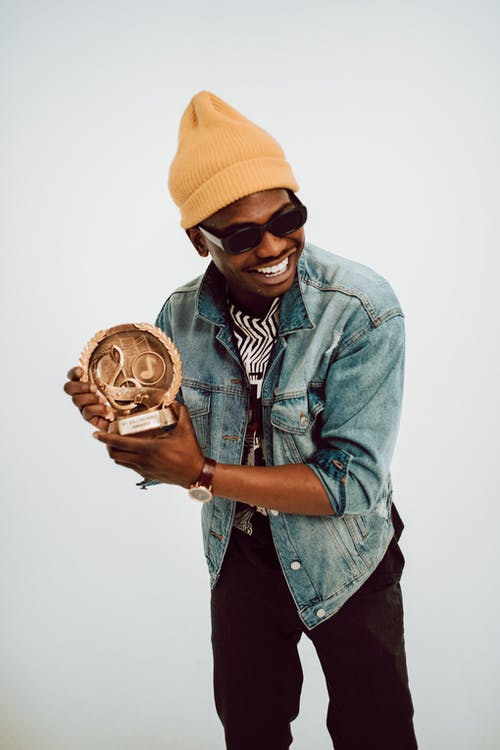 Man in Yellow Knit Cap and Blue Denim Jacket Holding Brown Wooden Round Ornament