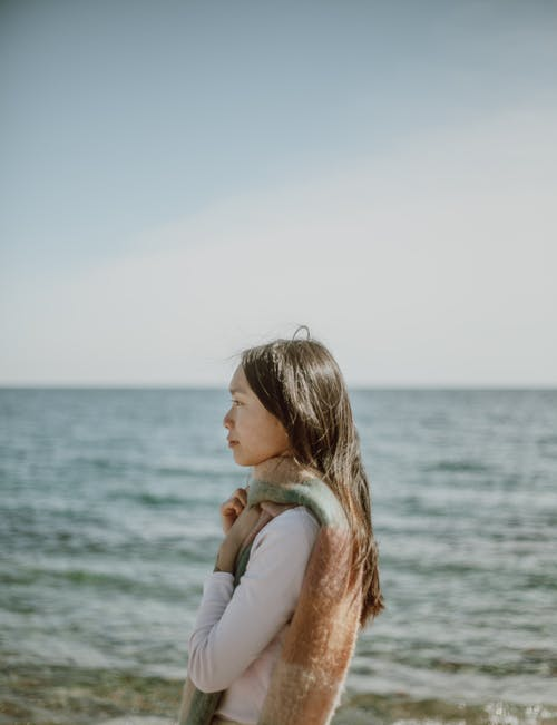 Serene Asian woman with long hair enjoying seascape