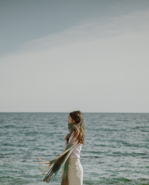 Young woman with waving scarf standing near sea