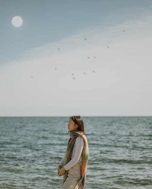 Side view of Asian female traveler in casual clothes and scarf standing near waving sea against flock of birds flying on sky