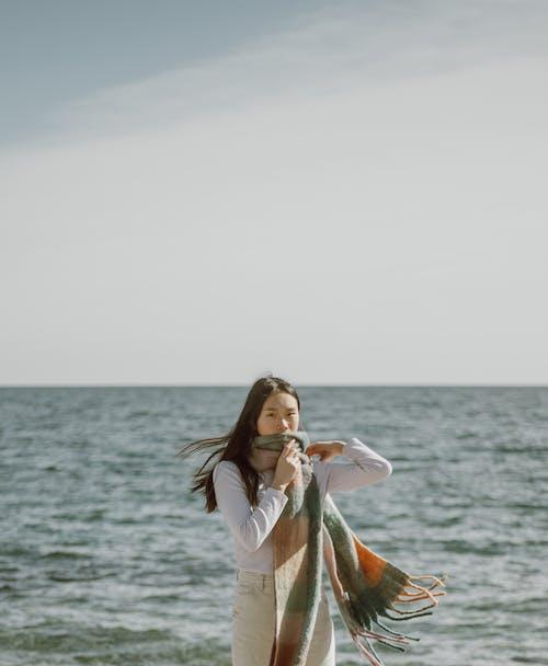 Peaceful ethnic woman wrapping in scarf on seashore