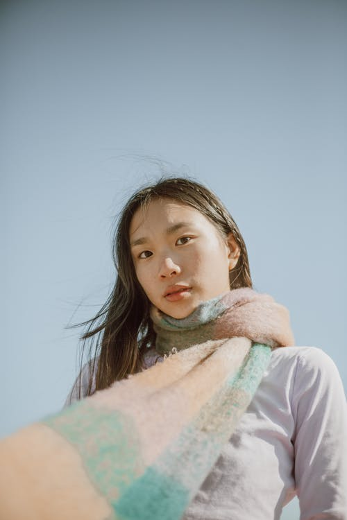 Low angle of Asian female with long dark hair wearing warm scarf standing against blue sky and looking at camera
