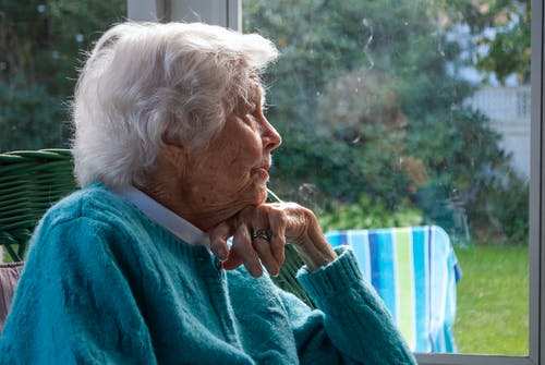 Side view of pensive senior female with white hair in warm sweater leaning on hand and looking away while resting on chair near window at home