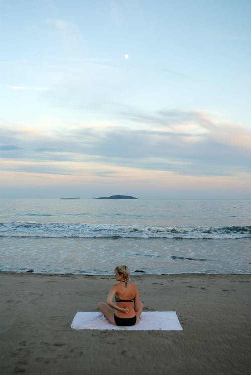 Anonymous lady in swimwear relaxing on sandy seashore at sundown