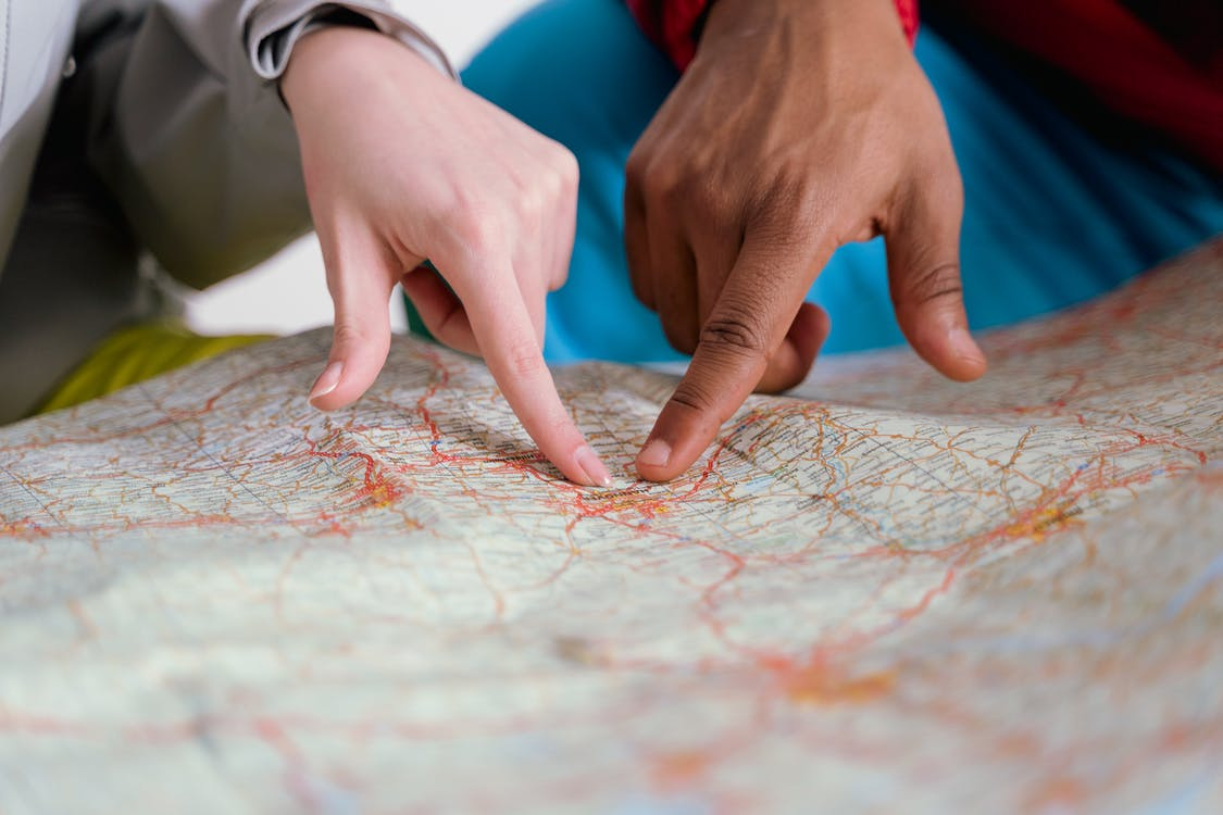 People Pointing Finger on Map