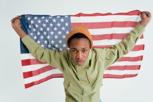 A Boy With Orange Beanie Holding An American Flag