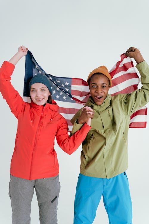 afrikalı amerikalı adam, amerikan bayrağı, beyaz kadın içeren Ücretsiz stok fotoğraf