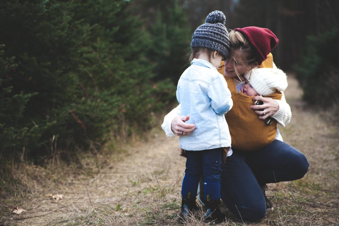 Woman With Brown Baby Carrier And Little Kid In White Jacket