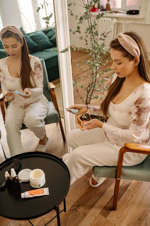 Woman Sitting on a Chair Putting Hand Cream