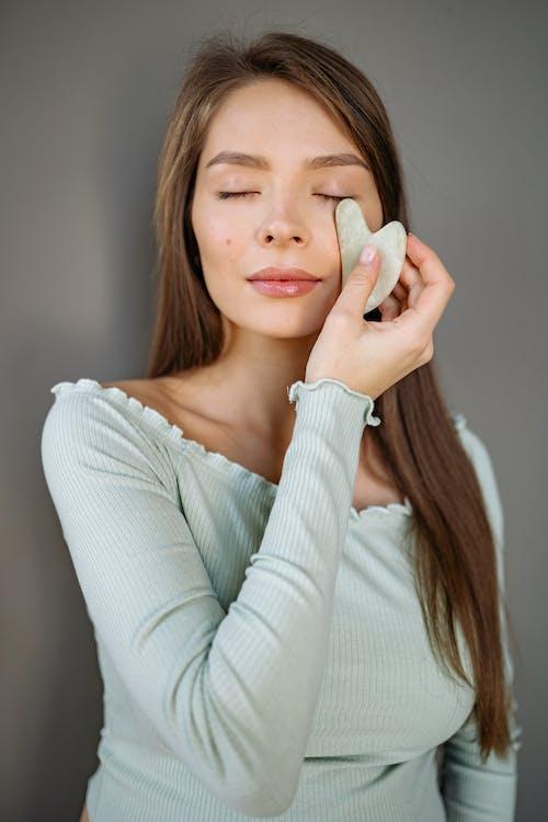 A Woman Using Jade Stone Massaging Her Cheek
