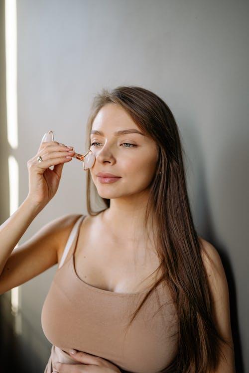 A Woman Using a Roller Jade on Her Cheek