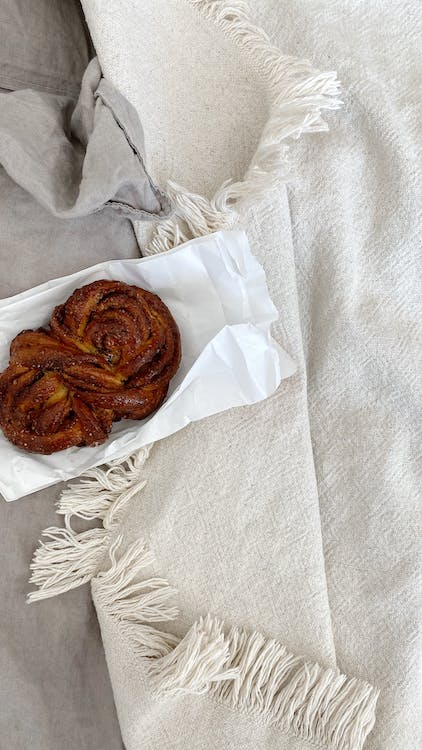 Delicious pastry placed on cozy bed near plaids
