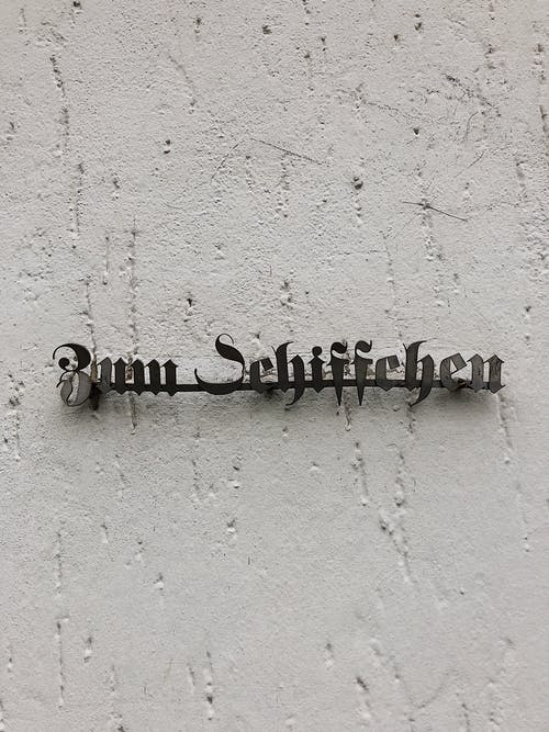 Black and white of creative inscription of name of restaurant attached to rough stucco wall on street of Dusseldorf