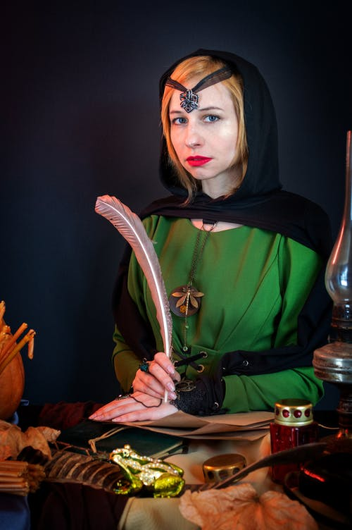 Female soothsayer in headscarf and amulets looking at camera while sitting at glass table with decorative frog