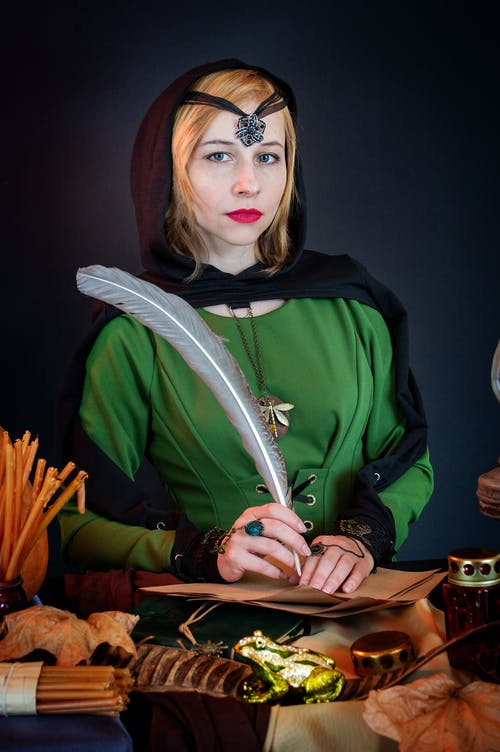 Fortune teller with feather at table on black background