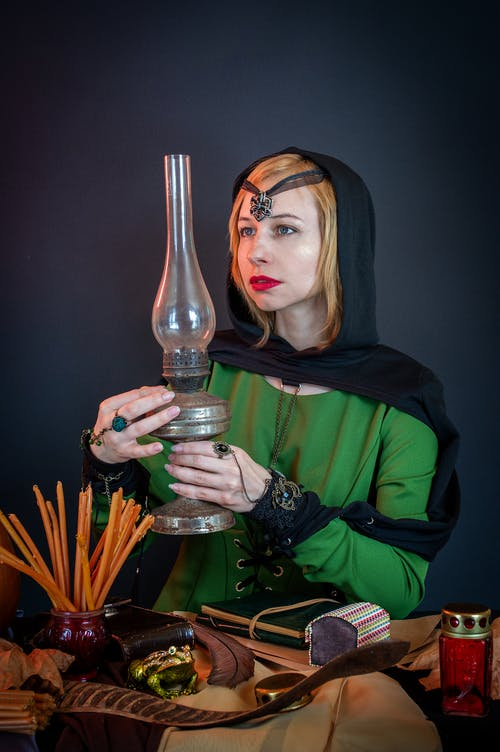 Young female fortune teller in amulet with aged kerosene lamp against wax candles and decorative snake on table