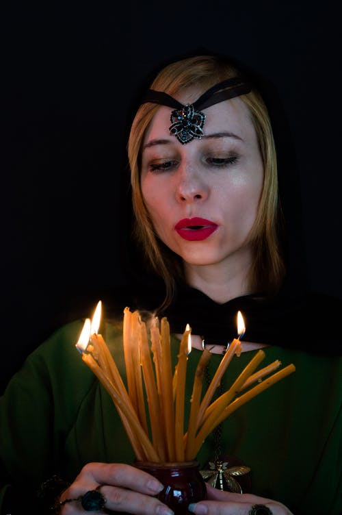 Female fortune teller with talisman on head blowing out flaming wax candles after predicting fate