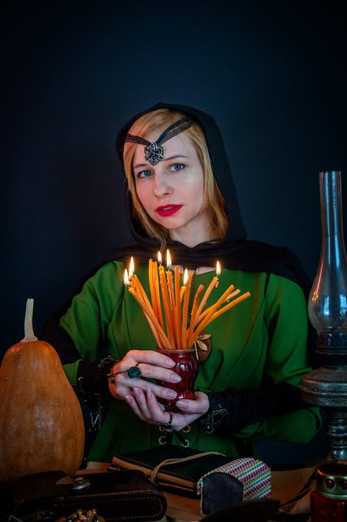 Young female soothsayer with talisman on head and flaming candles looking at camera against decorative pumpkin