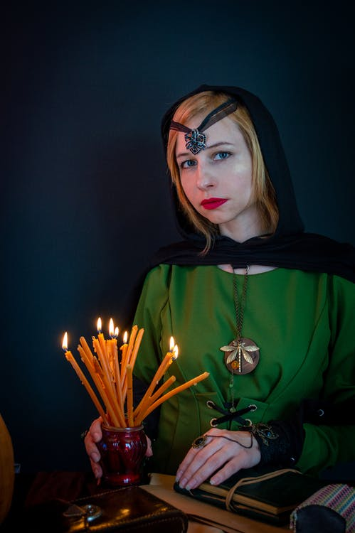 Soothsayer with flaming candles on black background