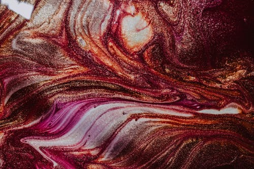 Abstract background of multicolored glossy paints splattered on canvas