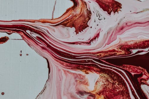 Top view of bright multicolored paints with glimmers smeared on white canvas as abstract background
