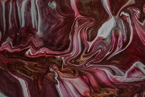 Swirling pattern of glossy vivid dyes as abstract background