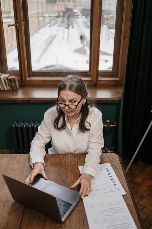 High-Angle Shot of a Woman in White Long Sleeves Using a Laptop