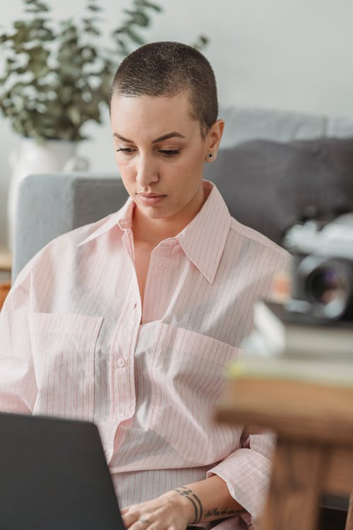 Focused young self employed lady with short hair in stylish clothes leaning on sofa while siting on floor and working remotely on laptop at home