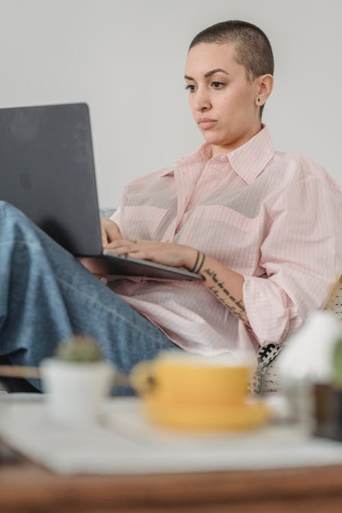 Serious young tattooed female freelancer with shaved head in casual clothes sitting on sofa and typing on netbook while working remotely from home