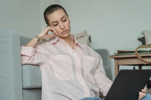 Pensive young self employed woman with short dark hair in casual clothes leaning on hand while sitting on floor near sofa during remote work on laptop at home