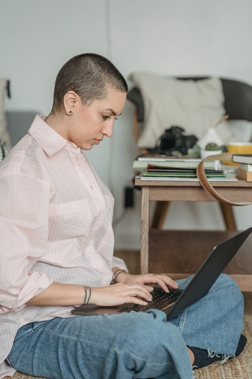 Side view of busy young female freelancer with short hair in casual outfit sitting on floor with crossed legs and browsing laptop while working remotely in light living room