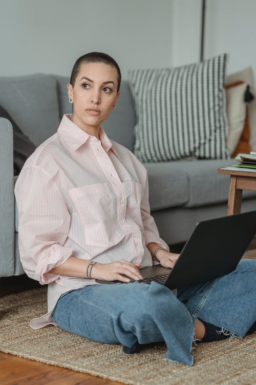 Pensive woman sitting on floor while working on laptop in living room