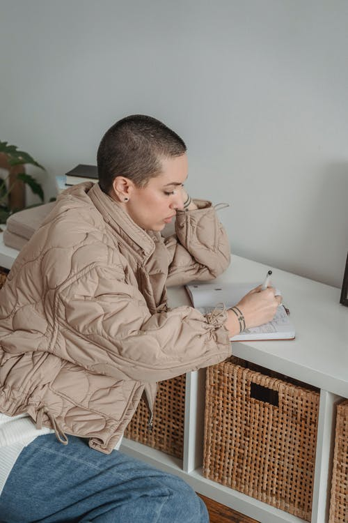 Side view of pensive female with short hair taking notes in agenda at table in house room on light background