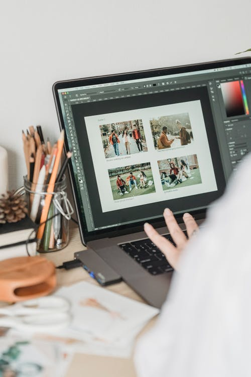 Crop unrecognizable female freelancer using touchpad while retouching photos on laptop during remote work at home