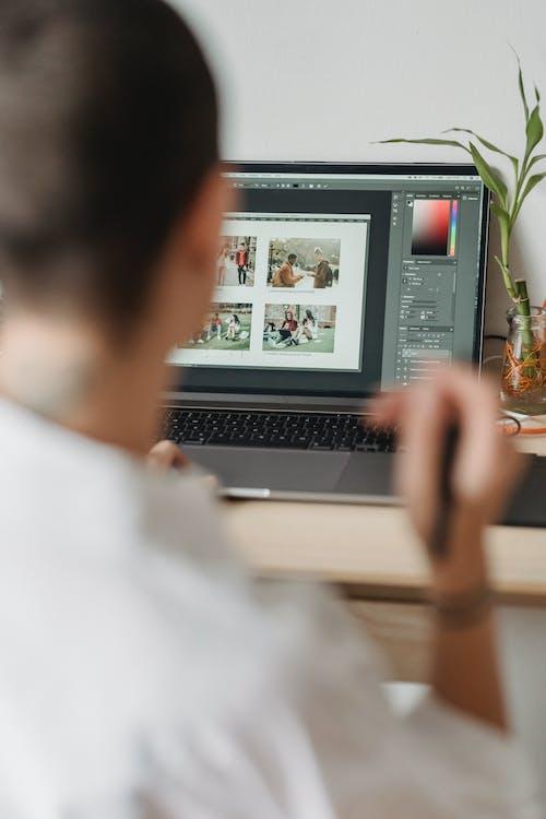 Crop faceless photographer browsing laptop and choosing photos
