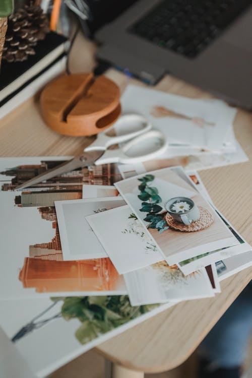 From above of various images scattered on wooden table near netbook for remote work from home