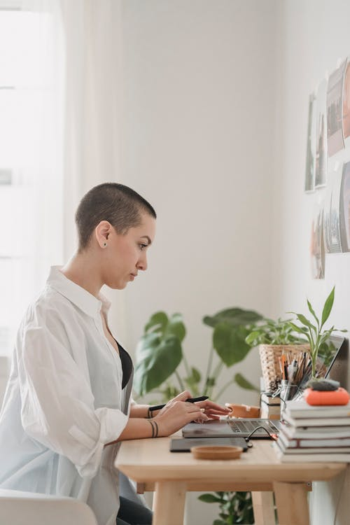 Serious woman browsing laptop while working attentively