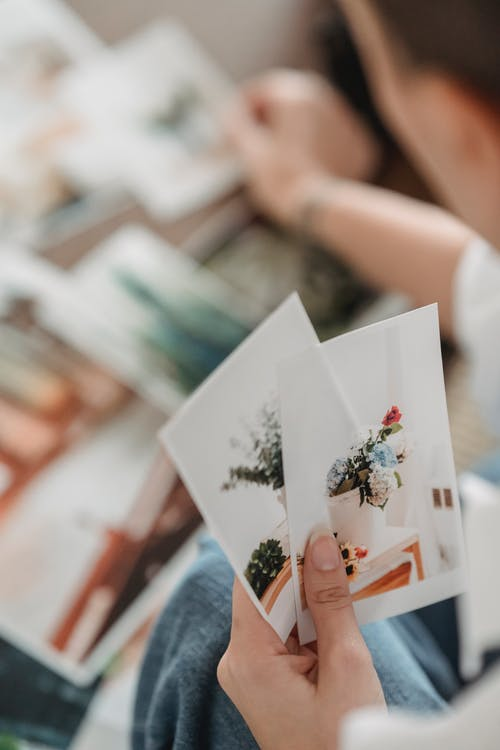 Woman selecting pictures placed on table