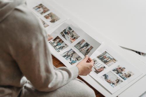 Crop unrecognizable woman looking through printed photos in album