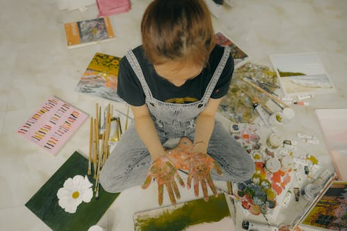 From above crop anonymous girl in casual jumpsuit demonstrating dirty hands while sitting on floor near paints paintbrushes and drawings