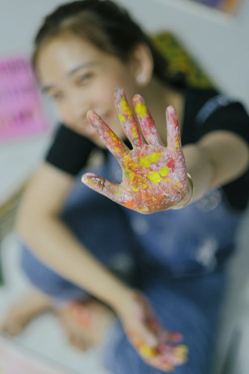 Crop happy girl showing hand in finger paints